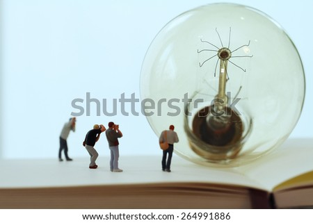 Creative idea concept - miniature photographer with vintage light bulb on open paper notebook - stock photo