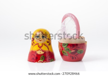 Creative idea for 'Birth control'. An open condom placed on a Russian doll. - stock photo