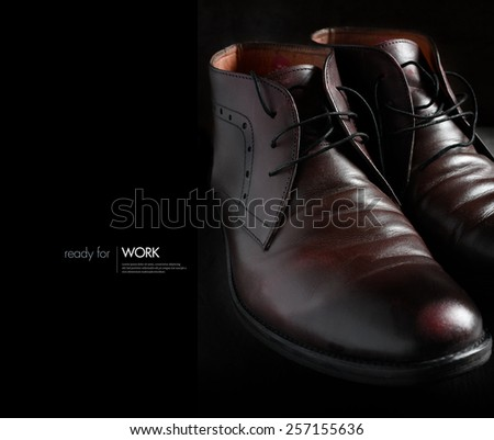 Creative image for work. Beautifully lit with natural light a pair of polished man's shoes against a dark background. Use for work, leaving home, travel, university, new job concepts. Copy space. - stock photo