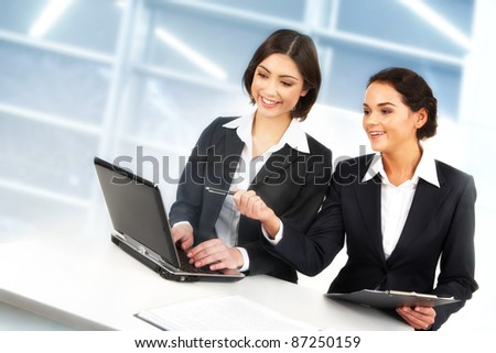 Creative image of two businesswomen working with laptop in office - stock photo