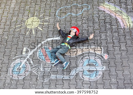 Creative leisure for children: Happy little child of four years in helmet having fun with motorcycle picture drawing with colorful chalks. Children, lifestyle, fun concept. - stock photo