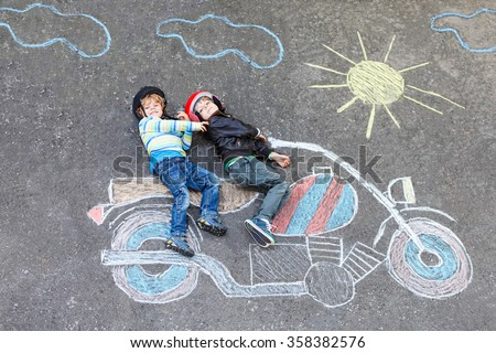 Creative leisure for children: two little funny friends in helmet having fun with motorcycle picture drawing with colorful chalks. Children, lifestyle, fun concept. - stock photo