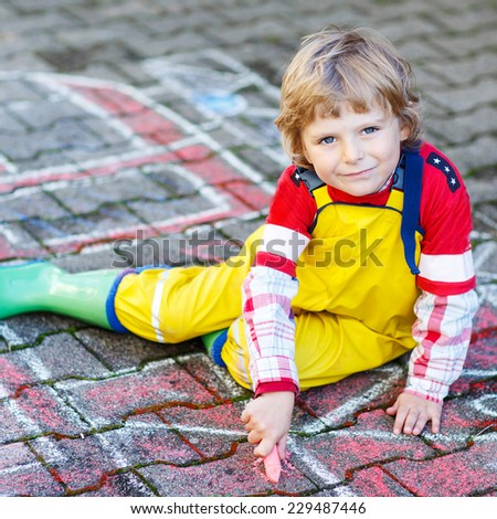 Creative leisure for kids: adorable child clothing as fireman having fun with fire truck picture drawing with chalk, outdoors. Dreaming of future profession. - stock photo