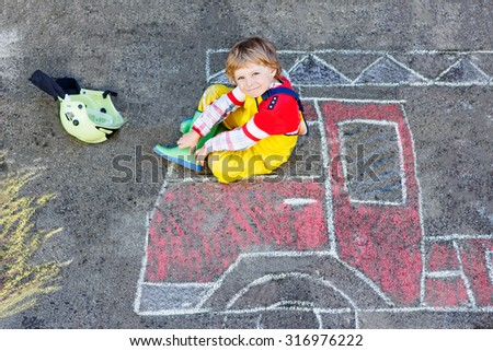 Creative leisure for kids: adorable child of four years having fun with fire truck picture drawing with chalk, outdoors. Dreaming of future profession. - stock photo
