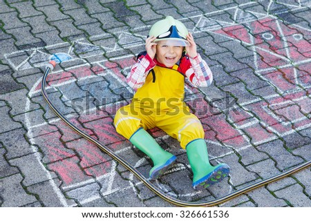 Creative leisure for kids: cute kid boy in helmet having fun with fire truck picture drawing with chalk, outdoors. Dreaming of future profession. - stock photo