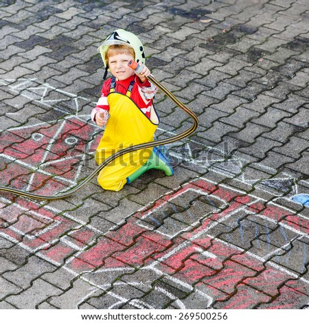 Creative leisure for kids: Funny little child of four years having fun with fire truck picture drawing with chalk. - stock photo