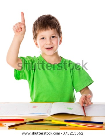 Creative little boy at the table with pencils, pointing up, isolated on white - stock photo
