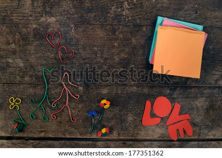 """Creative love story. Couple holding hands made from paper clips and and thumbtacks, next to blank editable post-its. The word """"Love"""" is written in paper letters. - stock photo"""