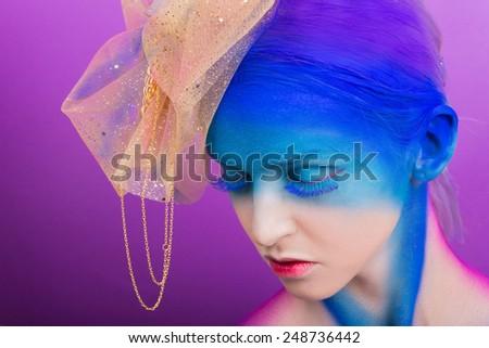Creative makeup. Airbrush. Blue, indigo, violet makeup. Seasoned professional creative eye make-up, hair. Golden headdress on the girl.  - stock photo