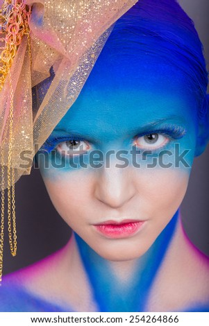 Creative makeup. Airbrush. Blue, indigo, violet makeup. Seasoned professional creative eye make-up, hair. Golden headdress on the girl.