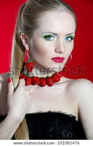 Creative makeup beauty shot of model with strawberries, passion and desire