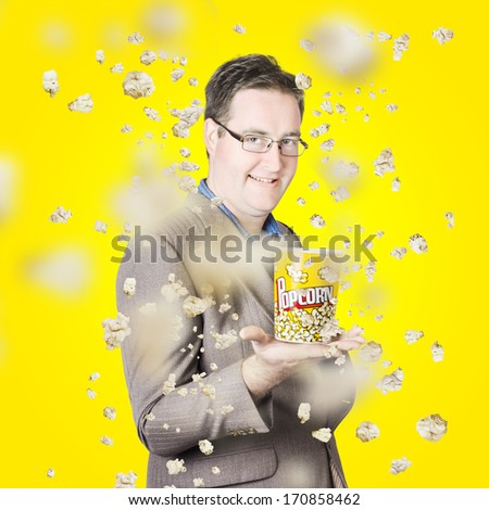 Creative movie portrait of a smiling man watching the fall of cinema popcorn on bright yellow background. Films and movies - stock photo