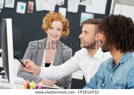 Creative multiethnic young business team at work in the office sitting in front of a large desktop monitor discussing a design initiative - stock photo