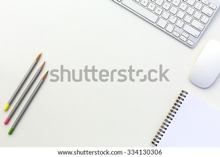 Creative Office Bright Table with Computer Keyboard Mouse Notepad and Three Color Pencils Top View with Copy Space - stock photo