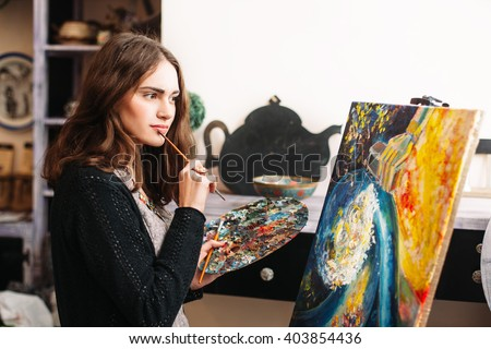 Creative pensive  painter paints a colorful picture. Closeup of painting process in art workshop Creative positive woman painter paints in her studio abstract picture.  - stock photo