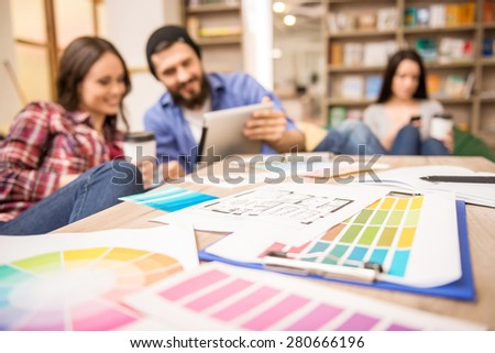 Creative people having coffee break at office and looking at tablet. - stock photo