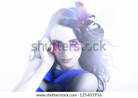Creative Portrait Of A Beautiful Woman With Wavy Brunette Hairstyle, Feather Headwear And Colourful Makeup Including Bright Eye Shadow, Glossy Lips And Dark Eyebrows - stock photo