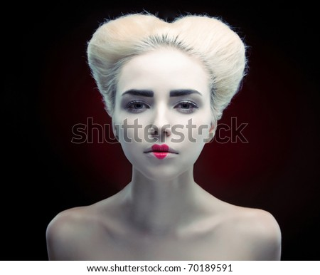 Creative portrait of a beautiful young girl with a heart painted on his lips, and hair in the shape of a heart