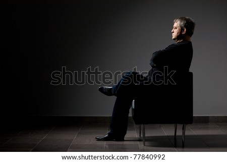 Creative portrait of middle-aged man sitting in a chair.