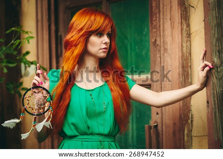 Creative Portrait of Redhead Young Woman in Green Dress with DreamCatcher in her Hands. Long Beautiful Red Hair. Selective focus. - stock photo