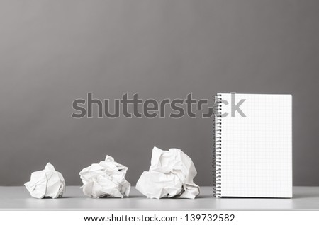 creative process. crumpled wads and notebook on gray - stock photo
