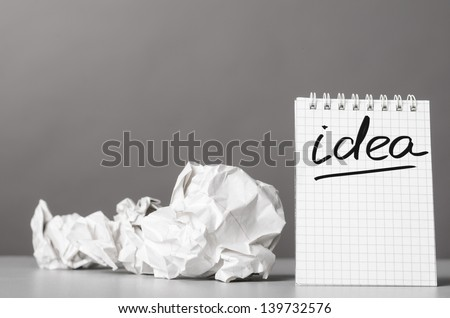 creative process. crumpled wads and notebook with word idea - stock photo