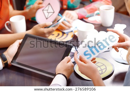Creative process. Selective focus on hands holding tablet with copy place and hands holding share icon, bright icons and cups and smartphone on the background  - stock photo