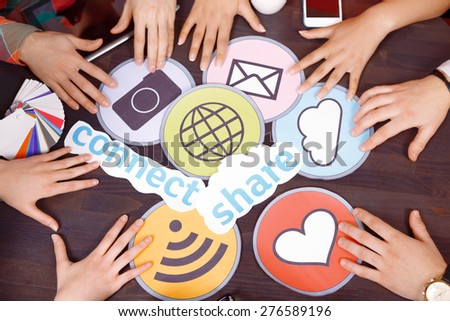 Creative process. Top view of bright icons of heart wifi message internet connect share cloud camera and pallet laying on the table and hands from all sides - stock photo