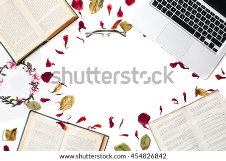 Creative profession. Frame of books, textbooks, laptop, glasses, leaves and petals isolated on white background. Flat lay, education concept - stock photo