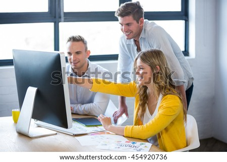 Creative smiling business people discussing over computer at desk in office - stock photo