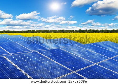 Creative solar power generation technology, alternative energy and environment protection ecology business concept: solar battery panels in yellow rural rape field against blue sky with sun light - stock photo