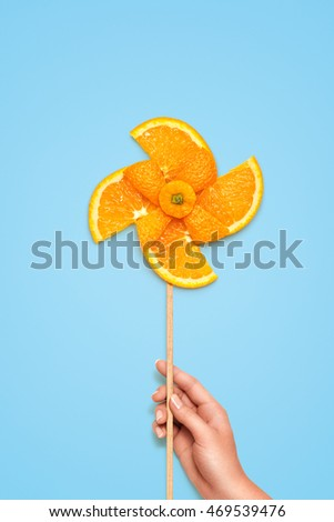 Creative still life of a yellow toy windmill made of fresh orange slices on blue background.