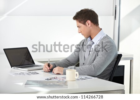 Creative student working with his laptop at desk