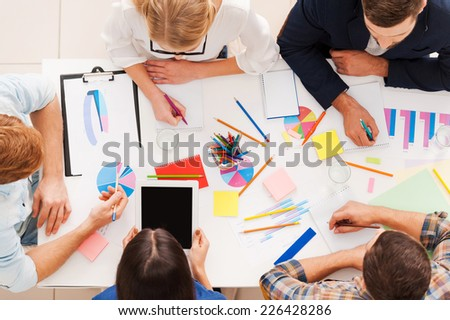 Creative team at work. Top view of business people in smart casual wear working together while sitting at the table - stock photo