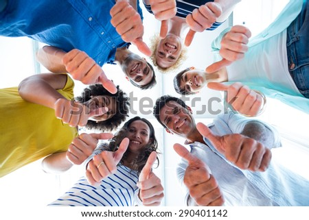 Creative team gesturing thumbs up while in circle - stock photo