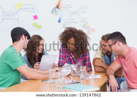 Creative team going over contact sheets in meeting in office with whiteboard - stock photo
