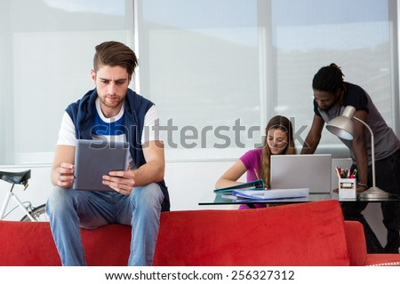 Creative team with digital tablet and laptop in office - stock photo