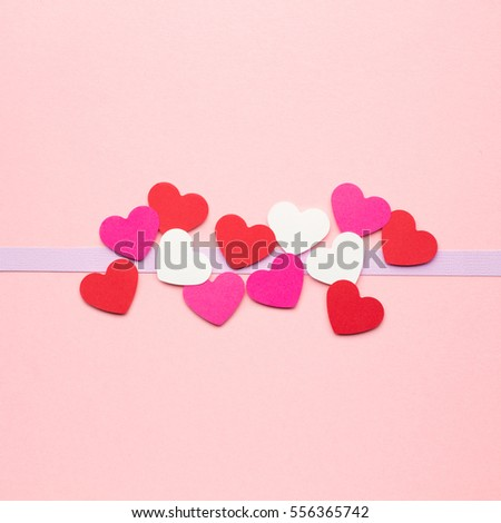 Creative valentines concept photo of hearts made of paper on pink background.