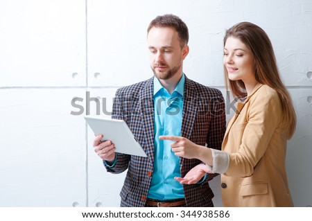 Creative work and technology. Smiling handsome man and woman using tablet computer while discussing something against white wall. - stock photo