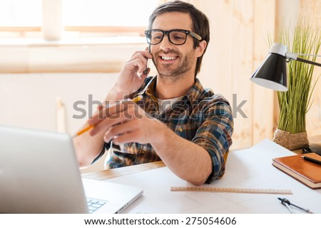 Creative worker. Cheerful young man talking on mobile phone and pointing at the laptop while sitting at his working place - stock photo