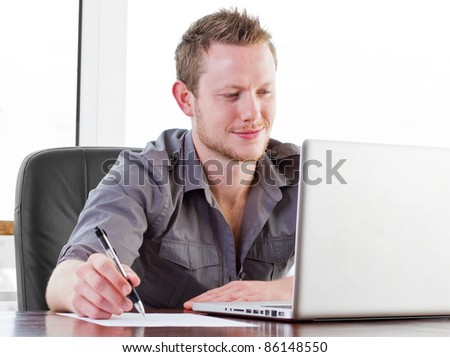 Creative worker smiling as he works on his laptop - stock photo