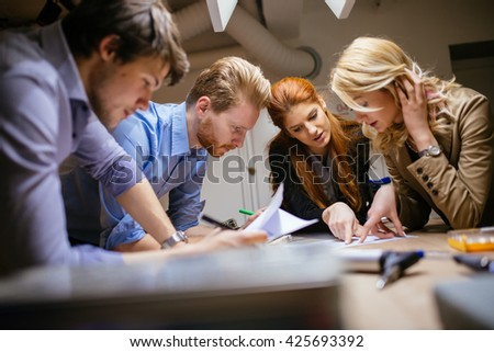 Creative workers designing and planing together in workshop - stock photo
