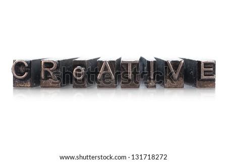 CREATIVE written in metallic letterpress typeface on a white background - stock photo