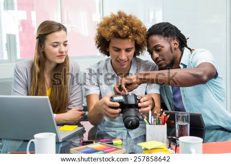Creative young business people looking at digital camera at office desk - stock photo