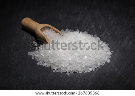 Creatively and Selectively Lit a Pinch of Rock Salt with Wooden Scoop against a Black Background - stock photo