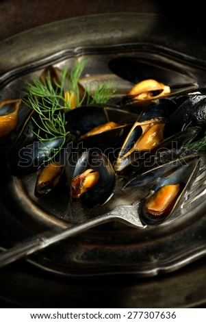 Creatively lit and focused Moules Mariniere, mussels steamed in white wine and garlic cream sauce in a rustic setting against a dark background. Copy space.  - stock photo