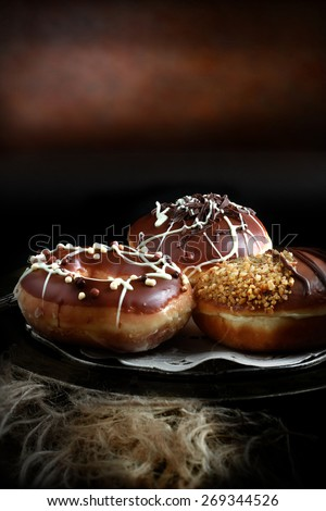 Creatively lit donuts smothered in thick chocolate, icing and toppings against a rustic background with copy space. The perfect image for your dessert menu cover design. - stock photo