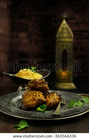 Creatively lit Indian Onion Bhajis with pilau rice against an authentically Indian dark, rustic styled background. The perfect image for your Indian menu cover design. Accommodation for copy space. - stock photo