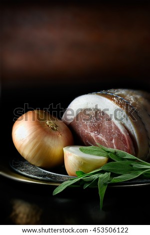 Creatively lit joint of prepared pork with sage and onion. The perfect image for your cooking preparation cover design. Copy space and selective sharp focus. - stock photo