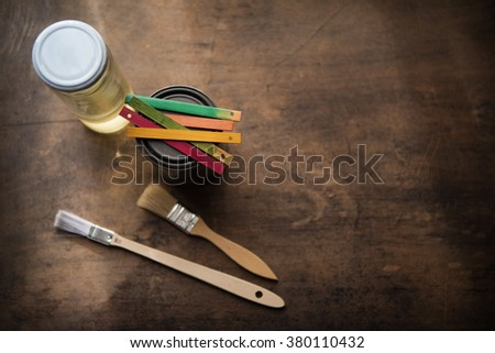 Creativity. Color samples on paint can. Color samples, paint, solvent and brush on an old wooden surface. Focus is on yellow color sample. Shallow depth of focus. - stock photo